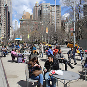 People relax in the spring sunshine at Flatiron Plaza, Manhattan, New York, USA. 26th March 2013. Photo Tim Clayton