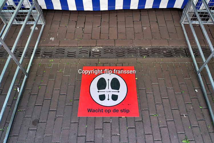 Nederland, Nijmegen, 11-5-2020 Bij een kraam op de markt, zijn matjes op de grond gelegd om de bezoekers te dwingen afstand van 1,5 ,anderhalve, meter te houden . Symbool,pictogram, associatie . Foto: Flip Franssen