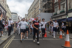 Licensed to London News Pictures. 11/07/2021. London, UK. Fans go wild as they gather in Leicester Square in London ahead of England's Euro 2020 finals match. England take on Italy in the Euro 2020 final at the iconic Wembley Stadium this evening. Photo credit: Alex Lentati/LNP