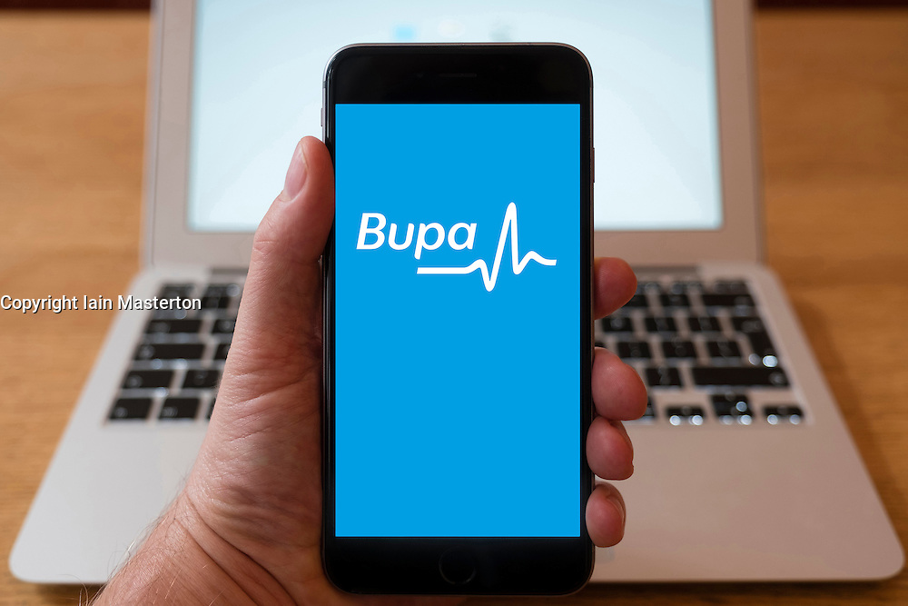 Using iPhone smartphone to display logo of BUPA, healthcare insurance provider