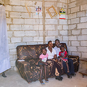 INDIVIDUAL(S) PHOTOGRAPHED: From left to right: Rebecca Msimuko, Sarah Msimuko, Samson Msimuko and Mary Mwele. LOCATION: Ten Miles, Lusaka, Zambia. CAPTION: Samson Msimuko and his family at their home in Ten Miles, Lusaka, Zambia. Samson completed his bricklaying training at the Build It Centre of Excellence with Build It International, a charity that trains unemployed young people in Zambia to become builders, while at the same time building vital schools and clinics in communities with little or nothing by way of resources.