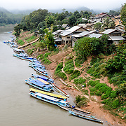 Numerous boats are moored along the town waterfront in Nong Khiaw in northern Laos. This shot, taken from the high bridge spanning the river, provides an elevated view of the waterfront, with the river at left and buildings at right.