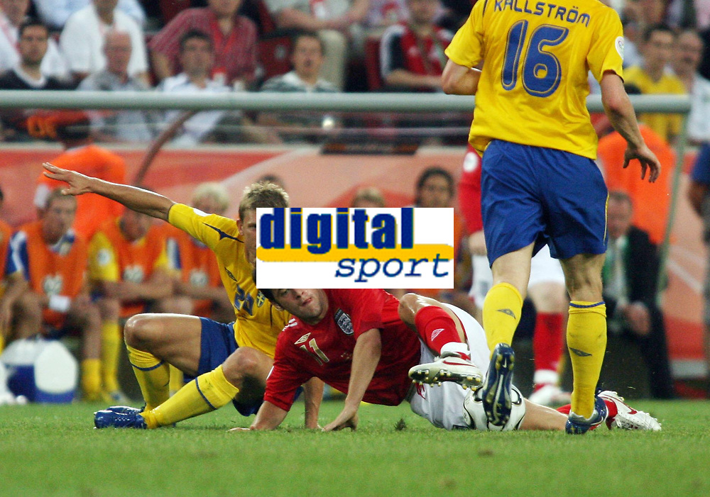 Photo: Chris Ratcliffe.<br /> Sweden v England. FIFA World Cup 2006. 20/06/2006.<br /> Marcus Allback of Sweden clashes with Joe Cole of England.