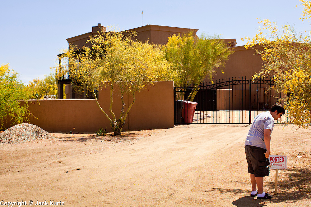 """22 MAY 2011 - SCOTTSDALE, AZ:  A man who refused to talk to the media puts a """"No Trespassing"""" sign in front of a home reportedly owned by Sarah Palin in Scottsdale, AZ. According to the Arizona Republic, Sarah Palin and her husband Todd Palin, bought the 8,000 square foot home for $1.695 million cash. The newspaper said the Palin's name does not appear on the paperwork and the home was bought by Safari Investments LLC out of Delaware. The paper said the deal """"appears designed to cloak the identity of a high-profile buyer."""" The home has six bedrooms, five bathrooms, a six car garage, swimming pool, spa, home theater, wine cellar and children's """"jungle gym"""" in the backyard. The home is surrounded by a tall wall with an electronic gate. Phoenix TV stations have reported that a black SUV with Alaska license plates has been seen entering and leaving the compound. People in the house have refused to comment on who owns the home. Neither Palin nor her husband have been seen at the home since news of the sale broke Saturday, May 21.   Photo by Jack Kurtz"""