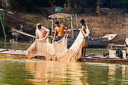 13 MARCH 2006 - CHAU DOC, AN GIANG, VIETNAM: Men haul a fishing net out of the Mekong River near Chau Doc in the Mekong River delta. The Mekong is the lifeblood of southern Vietnam. It is the country's rice bowl and has enabled Vietnam to become the second leading rice exporting country in the world (after Thailand). The Mekong delta also carries commercial and passenger traffic throughout the region.  PHOTO BY JACK KURTZ