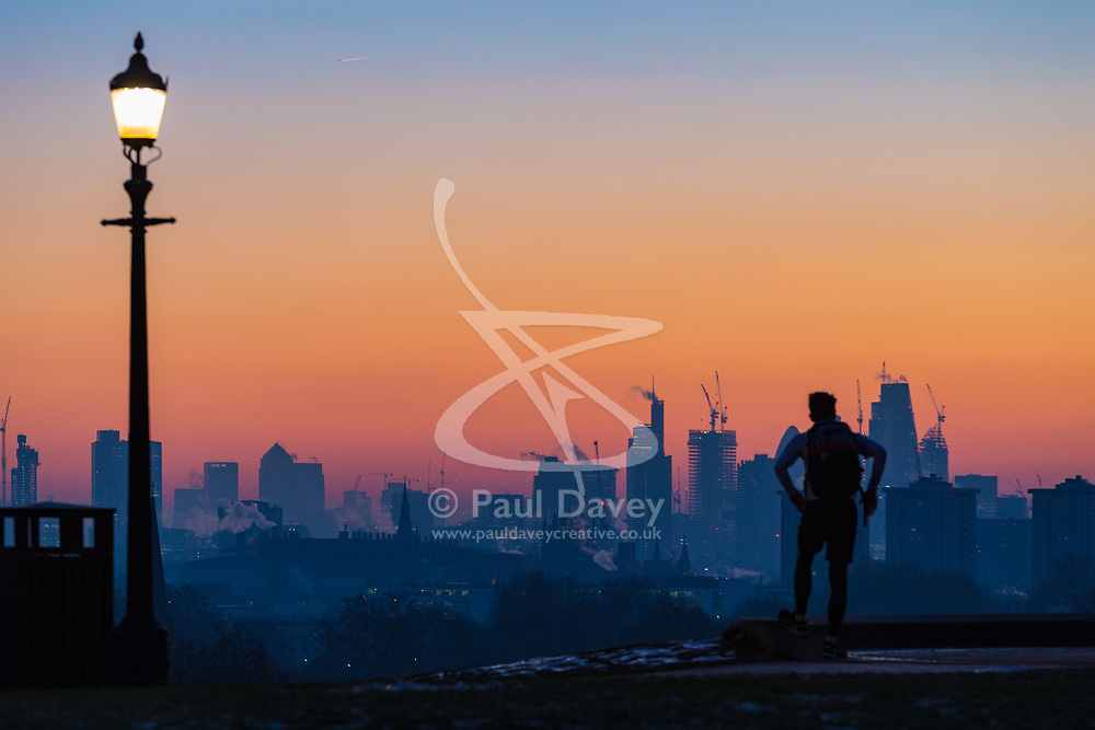 London, December 12 2017. An early riser awaits the sunrise on a clear very cold morning in London, seen from Primrose Hill in Camden. © Paul Davey