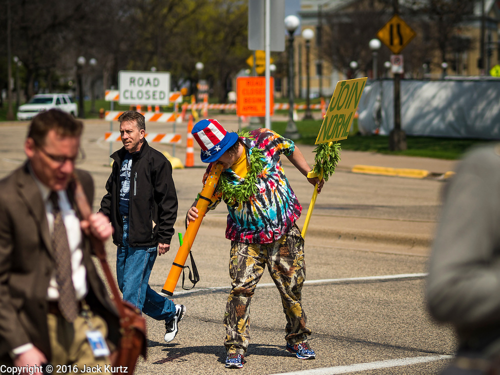 """20 APRIL 2016 - ST. PAUL, MN: A man who identified himself as """"Cool Breeze"""" inhales from a large """"bong"""" on his way to a marijuana legalization rally in St. Paul. About 100 people gathered at the Minnesota State Capitol in St. Paul and marched through downtown St. Paul calling for the decriminalization of marijuana. April 20 (4/20) has become a sort of counter culture holiday in the US, with marches in many cities calling for the legalization of marijuana.      PHOTO BY JACK KURTZ"""