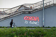 """A graffiti """"Corona is Fake"""" sprayed against a wall at the S-Bahn station Oberursel-Stierstadt."""