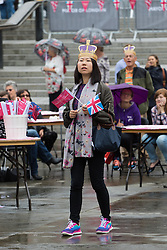 Trafalgar Square, London, June 12th 2016. Rain greets Londoners and visitors to the capital's Trafalgar Square as the Mayor hosts a Patron's Lunch in celebration of The Queen's 90th birthday. PICTURED: A woman strolls through the square as tourists and Londoners enjoy the occasion.
