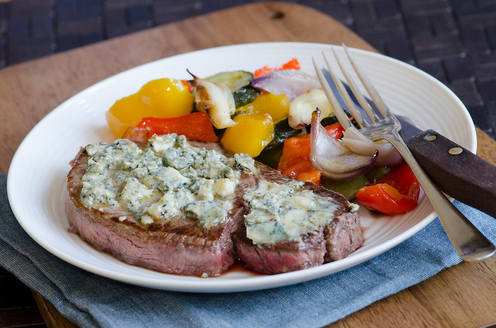 Steak topped with melted blue cheese with roast vegetables
