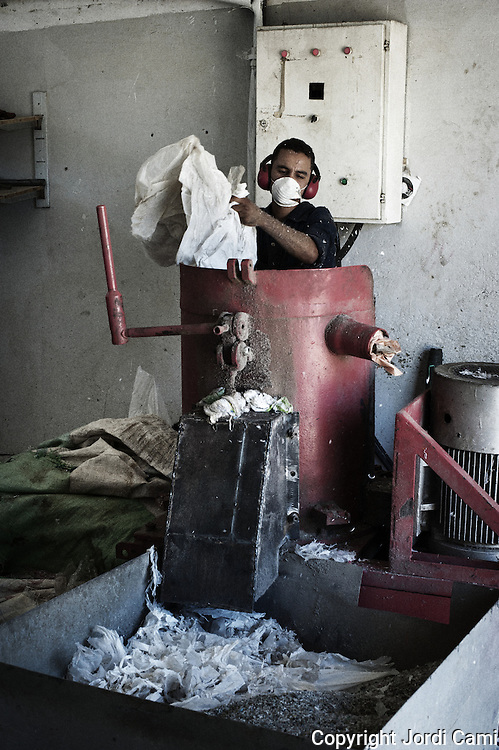 """Worker """"Zabbaleen"""" in a machine that shreds plastic for reuse, recycling plant Katameya, who heads the NGO APE on the outskirts of Cairo. . In the middle of Manshiet Nasr a Cairo neighborhood is located Mokattam settlement known as """"Garbage City"""" is inhabited by Zabbaleen, a community of about 45,000 Coptic Christians living for decades to recycle waste generated by the Egyptian capital: plastic, aluminum, paper and organic waste transformed into compost. Most part of the Association for the Protection of the Environment (APE), an NGO that works in the area, whose objectives are to protect the environment and improve the livelihoods of garbage scavengers in Cairo. According to the UN, the work is done in Mokattam is one of the ten best examples of world environmental improvement. El Cairo , Egipt, June 2011. ( Photo by  Jordi Camí )."""