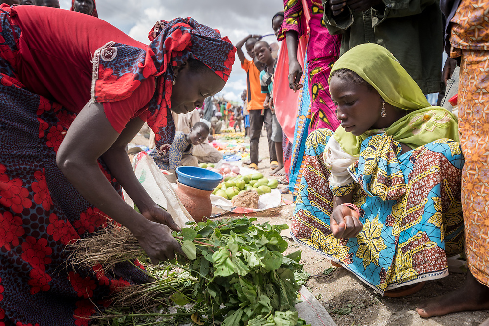 30 May 2019, Mokolo, Cameroon: Today is market day, and refugees and host communities alike gather to sell and buy goods in Minawao. Here, a woman sells vegetables. The Minawao camp for Nigerian refugees, located in the Far North region of Cameroon, hosts some 58,000 refugees from North East Nigeria. The refugees are supported by the Lutheran World Federation, together with a range of partners.