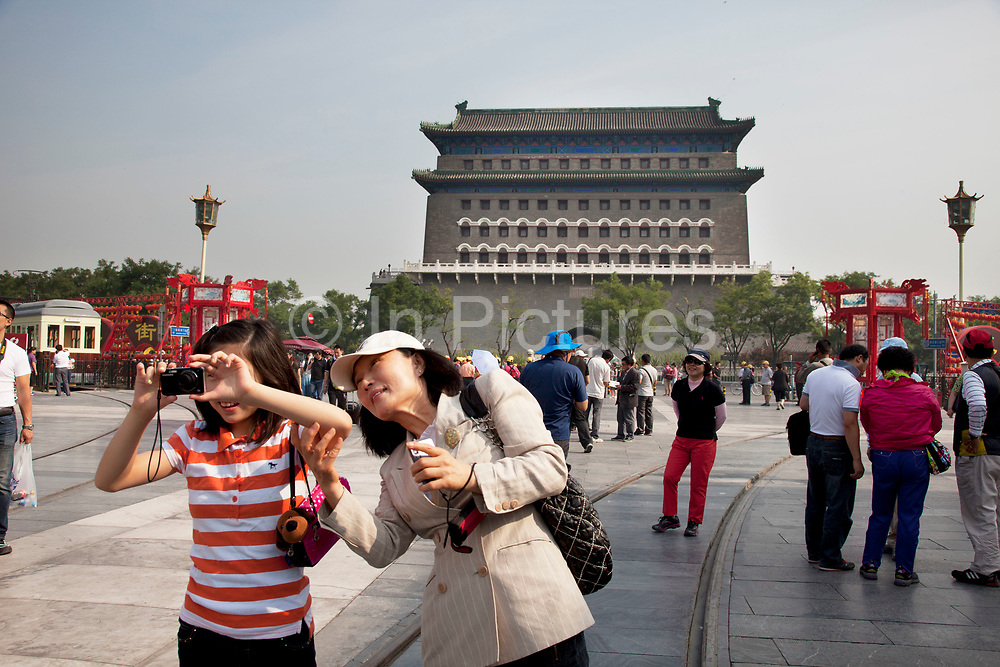 """Tourists at Qianmen (literally """"Front Gate"""") is a gate in Beijing's historic city wall. The gate is situated to the south of Tiananmen Square and once guarded the southern entry into the Inner City. Although much of Beijing's city walls were demolished, Qianmen remains an important geographical marker of the city. The city's central north-south axis passes through Zhengyangmen's main gate. It was formerly named Lizhengmen meaning """"beautiful portal"""". Zhengyangmen was first built in 1419 during the Ming Dynasty and once consisted of the gatehouse proper and an archery tower."""