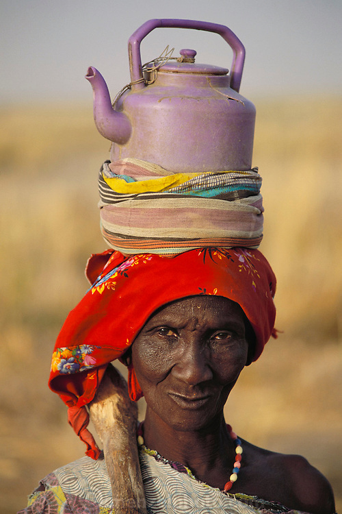 A woman carrying water in a plastic teapot in a traditional manner walks to the city of Djenne, Mali, on market day.  Published in Material World, page 20. Material World Project.
