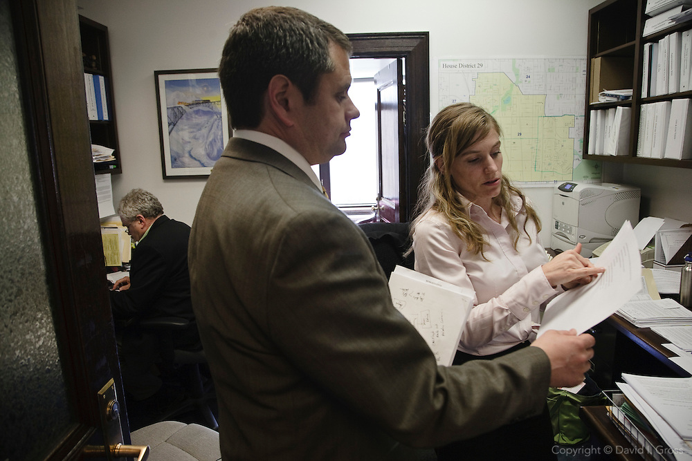 Alaska Representative Chris Tuck (D) and his aide Aurah Landau discuss how to get his bill out of the scheduling committee to the floor for a vote. Aide Gene White works in the background.