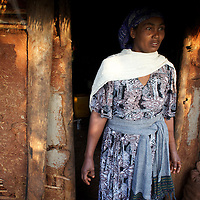 Bayush stands outside her home. <br /> <br /> Bayush Kassan (age 37) lives in the village of Amba Sebat, 20km from the town of Assosa with her daughter Genet (age 14) and son Destaw (age 11) in a small thatched hut without running water or electricity. Bayush is part of a cooperative of 31 women who collectively own land on which they farm vegetables. She grows sesame and other oil-seeds and her village cooperative is part of the Assosa Farmers Multipurpose Cooperative Union. The Union buy's Bayush's seed for almost double the average price paid to her by private traders. <br /> <br /> Growing oil seeds presents challenges for the famers of Assosa in western Ethiopia. Many of the most vulnerable are forced to sell to when they cannot be guaranteed a good price for their product. Farms are often located in isolated areas which entails huge amounts of time and effort simply getting seeds to market. Many farmers do not have the resources to properly invest in their land and are tied into exploitative loan arrangements with brokers that deny them the chance to take proper control of their farms. And, as with other agricultural products, it is those agents that process the seeds into oil that secure the greatest profit, very little of which trickles down to benefit the farmer.<br /> <br /> In response to these pressures, twenty farming cooperatives have formed the Assosa Farmers Multipurpose Cooperative Union. By working together, individual farmers are able to pool their resources and squeeze out exploitative agents and brokers. The Union has sufficient capital that it can afford to wait for prices to reach a level at which it is profitable to sell seeds to market. The Union provides loans to constituent members together with training and advice to help farmers make better use of their land. And by collectively hiring vehicles through the Union, farmers need not spend so much time ferrying their produce to market. <br /> <br /> All these measures benefit farmers and have now provided the Assosa Farmers Multipurpose C