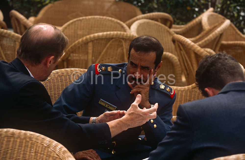 A doubtful-looking miitary officer from an unknown foreign state possibly Kuwait listens to an explanation from a western genleman at the BAE Systems corporate exhibition chalet during the Farnborough Air Show, on 20th June 2002, at Farnborough, Hampshire, England.