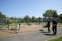 © Licensed to London News Pictures. 23/06/2020. London, UK. A couple wearing face coverings walk past a playground in Chestnuts Park, north London, which has been closed and fenced since 23 March following the COVID-19 lockdown. Outdoor gym will re-open from 4 July as Prime Minister Boris Johnson outlines the plans to restore normal life after three months of coronavirus lockdown. Photo credit: Dinendra Haria/LNP