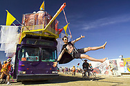 BLACK ROCK CITY, NV - SEPTEMBER 1:  Participants of Burning Man festival climb aboard a bus to take a tour of the temporary art instillations around Black Rock City, Nevada on September 1, 2005.  The bus, a work of art itself, dangles one Burning Man participant as 'bait' from a climbing rope in front of the driver.  Participation in the event is encouraged for every member of Black Rock City. (Photo by, Jonathan Kingston/Aurora)