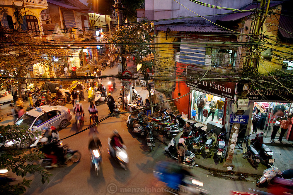 Evening traffic winds through a street in the old quarter section of downtown Hanoi.