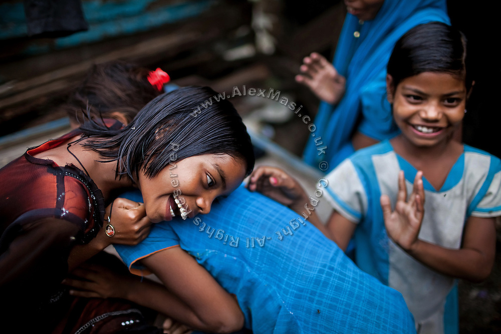 Jyoti, 10, (left) is embracing her older sister Arti, 15, while Poonam, 9, (right) is playing around next to them, in the front yard of their newly built home in Oriya Basti, one of the water-contaminated colonies in Bhopal, central India, near the abandoned Union Carbide (now DOW Chemical) industrial complex, site of the infamous '1984 Gas Disaster'.