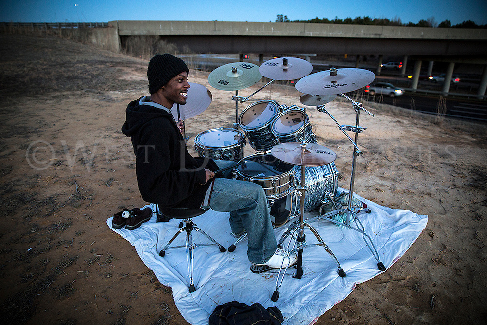 Kevin Bryant, of Raleigh, plays his drum kit along the side of I-540 at the Lumley Rd. exit on Feb. 24, 2014. Bryant chose this spot to play his drums because he received several complaints from neighbors and decided that along the interstate was good enough place as any due to the high volume of traffic noise. A few NC State Highway Patrol troopers have approached Bryant, who were just checking on him for safety concerns, but stated that he was not breaking any laws in playing along the side of the interstate and actually hung around to hear him play.