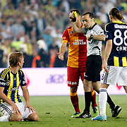 Referee's Cuneyt Cakir (2ndR) show the yellow card to Fenerbahce's Dirk Kuijt (L) during their Turkish superleague soccer derby match Fenerbahce between Galatasaray at the Sukru Saracaoglu stadium in Istanbul Turkey on Sunday 12 May 2013. Photo by Aykut AKICI/TURKPIX