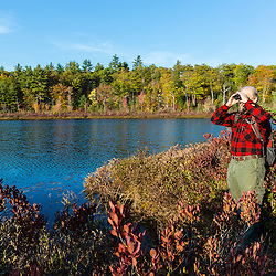 A man watches for birds at Round Pond in Barrington, New Hampshire.