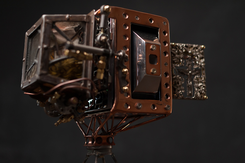 """""""Us & Them"""" camera, side view. <br /> The """"Us & Them"""" Camera made for this project is constructed from aircraft aluminum, titanium, steel, brass, copper, silver and glass. The camera contains artifacts that relate the subject of """"Us & Them"""". In the front of the camera hangs a silver crucifix that once belonged to Eva Braun (Adolf Hitlers wife), and has Evas monogram on the back. In the three silver pyramids on the top and sides of the camera, are chambers containing a human artifacts from the Vietnam war. They were donated by a U.S. Vietnam Vet, and were part of his """"proof of kill box"""" where he was required to take a body part from everyone he killed during the war. The back of the camera is a glass and rusty steel chamber. All of the glass I found in the Palestinian territories. Inside the chamber is an armband from WWII with a yellow Star of David on it. On the left side of the armband is a red stamp signifying that the owner of the armband was a registered Jew with the Nazi party. And wrapped around the armband is barbed wire that I picked up at the Israeli/Syrian border and was from the 1967 Six Day War. Interestingly while I was at the Syrian border, I experienced a massive air strike and bombing campaign from U.S. or Russian forces on a town close to the border. You could also hear antiaircraft fairly close to our position."""