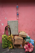 Imported bananas and other expensive sundries on display against a pink painted wall in a side street of Male, Maldives