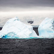 An iceberg floats in the freezing waters of Curtis Bay on the Antarctic Peninsula. While two separate sections appear above the water, the sections are connected by a much larger single section underneath the water.