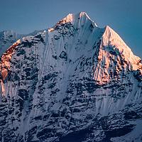 Evening light bathes Mount Kangtega towers in the Khumbu Region in Nepal.