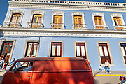 A red Volkswagen bus parked outside the colonial style City Hall in the central historic district of Coatepec, Veracruz State, Mexico.