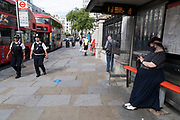 Woman wearing a colour co-ordinated face mask under coronavirus lockdown on Strand on 1st July 2020 in London, England, United Kingdom. As the July deadline approaces and government will relax its lockdown rules further, the central London remains very quiet, while some non-essential shops are allowed to open with individual shops setting up social distancing systems.