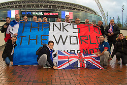 Wembley Stadium, London, November 17th 2015. Hours befor kick-off French and England fans begin to gather outside Wembley Stadium as both England and France national teams are poised to play in an emotional tie just days after the tragic death of 130 people in the Paris Islamist attacks. PICTURED:  French fans unfurl a giant flag thanking the world for their solidarity. // Licencing Contact: paul@pauldaveycreative.co.uk Mobile 07966 016 296