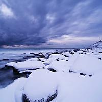Snow covered rocks at Unstad beach, Vestvågøy, Lofoten islands, Norway