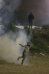 """© Licensed to London News Pictures . 23/10/2016 . Calais , France . A man picks up a tear gas canister , fired by riot police , and throws it back , at the Calais migrant camp known as """" The Jungle """" , in Northern France , on the evening before the start of the eviction and destruction of the camp . Photo credit: Joel Goodman/LNP"""