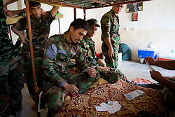 © Licensed to London News Pictures. 29/06/2014. Khanaqin, UK Khanaqin, Iraq. A Kurdish peshmerga fighters relax by playing cards on bunk beds at a peshmerga base in Khanaqin, Iraq.<br /> <br /> The peshmerga, roughly translated as those who fight, is at present engaged in fighting ISIS all along the borders of the relatively safe semi-automatous province of Iraqi-Kurdistan. Though a well organised and experienced fighting force they are currently facing ISIS insurgents armed with superior armament taken from the Iraqi Army after they retreated on several fronts. Photo credit : Matt Cetti-Roberts/LNP