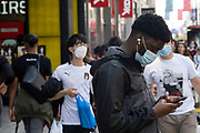 Young man looks intently at his smartphone as the national coronavirus lockdown three eases towards the planned Freedom Day in just over two weeks, and people, many of whom are still wearing face masks while out on the street, come to Oxford Street shopping district on 22nd July 2021 in London, United Kingdom. Now that the roadmap for coming out of the national lockdown and easing of restrictions is set, dome medical professionals are suggesting thatsome safety measures are kept in place because of the increase in the Delta variant.