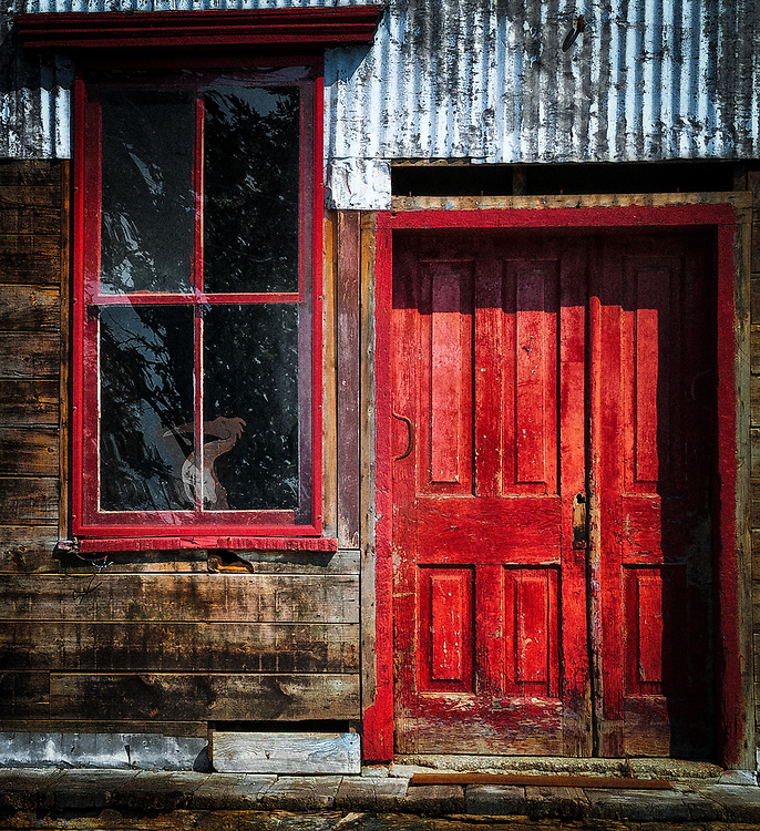 Deep, rich colours adorn a once familiar and heavily used mill doorway. An incongruous piece of art, a pelican, sits behind the adjacent window. A new vocation?