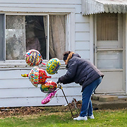 Helen Stahl, 100, watches as one of the attendees adds more balloons in front of her home in Fayette, Ohio, on Tuesday, April 14, 2020. Winameg Christian Church members and people in the community put together a parade to celebrate Stahl's birthday today. THE BLADE/KURT STEISS