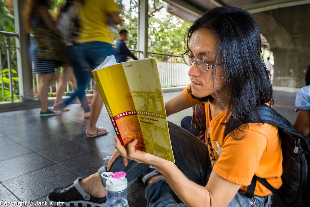 """31 MAY 2014 - BANGKOK, THAILAND: A man sits in the Skywalk between the BTS Skytrain Siam and Chit Lom stations to silently read George Orwell's """"1984"""" and other books about civil disobedience and nonviolent protest. The protests are based on the """"Standing Man"""" protests that started in Turkey last summer. Authorities made no effort to stop the protest or interfere with the people who were reading. Bangkok was mostly quiet Saturday. There were only a few isolated protests against the coup and military government.    PHOTO BY JACK KURTZ"""