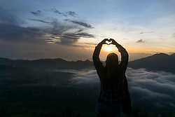 Silhouette of a young woman fingers forming a heart at dawn, Uluwatu, Bali, Indonesia