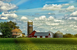 Sunlight peeks through the clouds of this rural farm scene just after a brief afternoon storm shedding light rays along the barn and farm land.