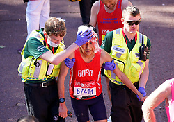 A runner is helped by paramedics after finishing the Virgin Money London Marathon. Picture date: Sunday October 3, 2021.