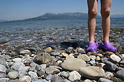 Greece, Thessaly, peninsula Pelion, Concept Holiday image of the legs of a young girl standing in the shallow water of the Mediterranean Sea