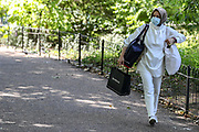 A woman is seen wearing face surgical mask as she walks through St James' Park in Central London on Monday, June 22, 2020, meanwhile, some others appear to be enjoying a day of leisure and what it appears to be challenging the two-metre social distancing rule, which will be under review as the UK relax coronavirus lockdown measures that implemented to stem the spread of the virus. The UK's coronavirus death toll has passed more than 40,000, according to the latest government figures. A total of 40,261 people have died in hospitals, care homes and the wider community after testing positive for the virus. (Photo/ Vudi Xhymshiti)