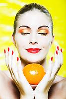 beautiful caucasian woman portrait smelling a citrus fruit pleasure smile studio on yellow background