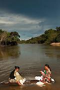 Amerindian doing laundry in the Rupununi River<br /> Karanambu Lodge<br /> Rupununi<br /> GUYANA<br /> South America