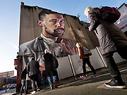 """The Seedhead Arts Street Art Walking Tour group approaches a wall to get a closer look in the Cathedral Quarter of Belfast November 11, 2018. """"Lobster Pot"""" was created by Sam Bates, aka Smug, an Australian native who now lives in Glasgow. Smug stayed an extra day in Belfast to repaint the lobster that the chef holds in order to get it just right. Three weeks later, the building's owner erected a fence that covers the lobster. The uncertain future of street art offers a transitory allure."""